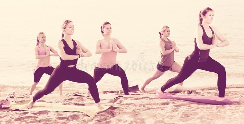 Γυναίκες που ασκούν τη θέση γιόγκας στην αμμώδη παραλία στοκ εικόνες