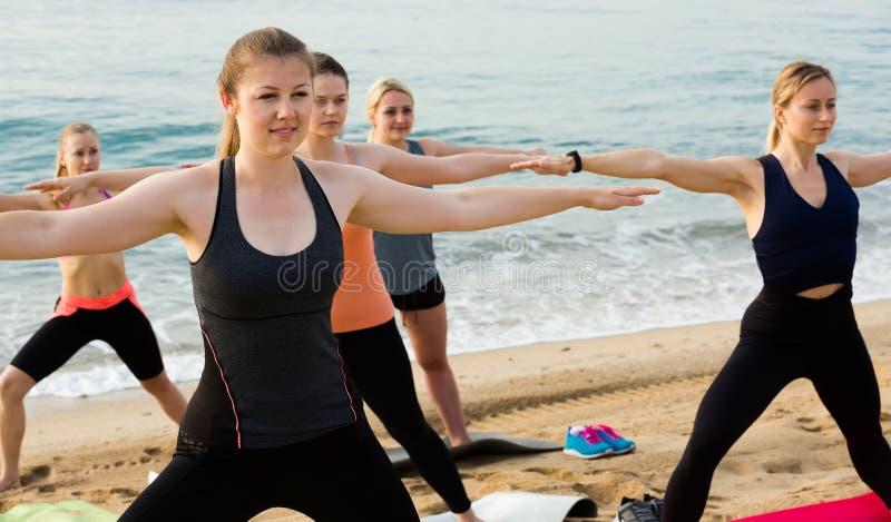 Γυναίκες που ασκούν τη θέση γιόγκας στην παραλία θάλασσας στοκ φωτογραφία με δικαίωμα ελεύθερης χρήσης