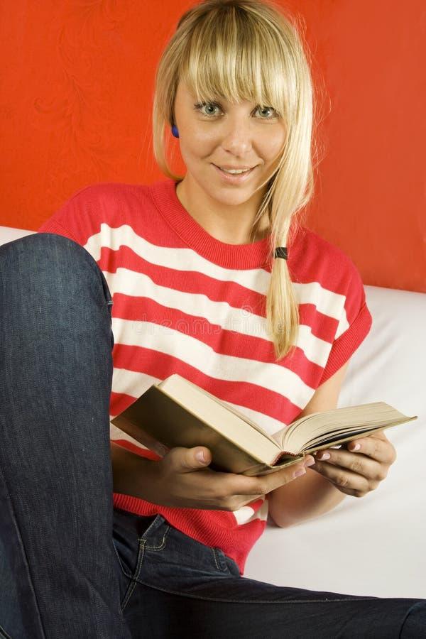 Γυναίκες που διαβάζουν ένα βιβλίο στον καναπέ στοκ φωτογραφία