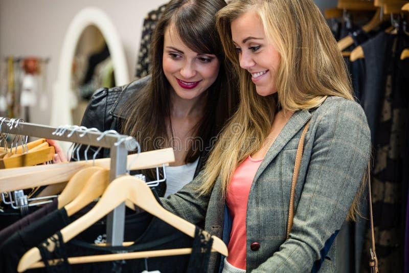 Γυναίκες που επιλέγουν ένα φόρεμα ψωνίζοντας για τα ενδύματα στοκ εικόνες