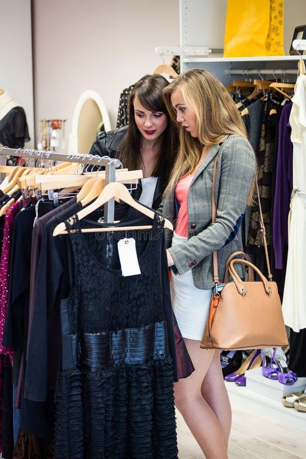Γυναίκες που επιλέγουν ένα φόρεμα ψωνίζοντας για τα ενδύματα στοκ φωτογραφίες