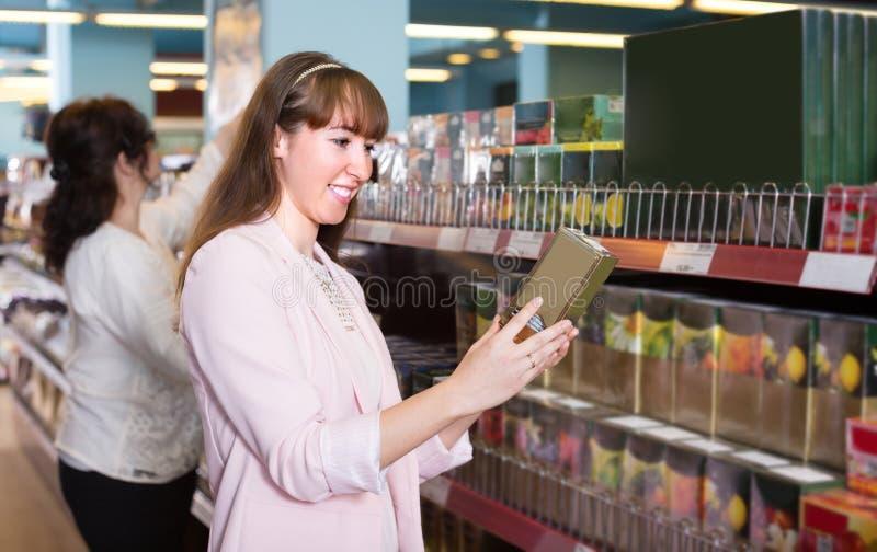 Γυναίκες που επιλέγουν το τσάι στο παντοπωλείο στοκ εικόνες