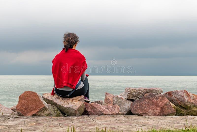 Γυναίκες που κάθονται στο βράχο κοντά στη λίμνη στοκ φωτογραφία με δικαίωμα ελεύθερης χρήσης