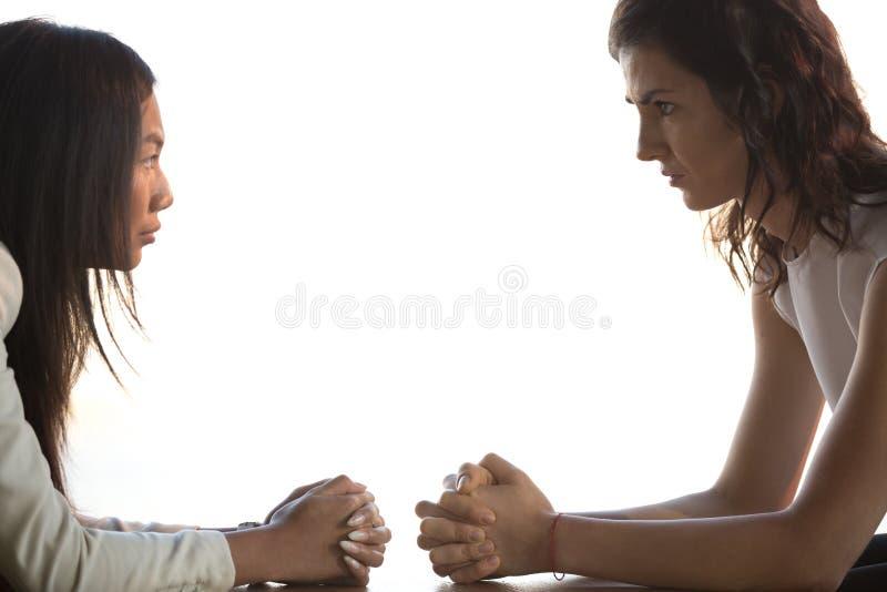 Γυναίκες που κάθονται στο γραφείο που κοιτάζει επίμονα το ένα στο άλλο unkindly στοκ φωτογραφία με δικαίωμα ελεύθερης χρήσης
