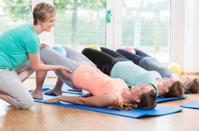 Γυναίκες που κάνουν τις ασκήσεις για το πάτωμα λεκανών στη μεταγεννητική οπισθοδρόμηση γ στοκ εικόνες