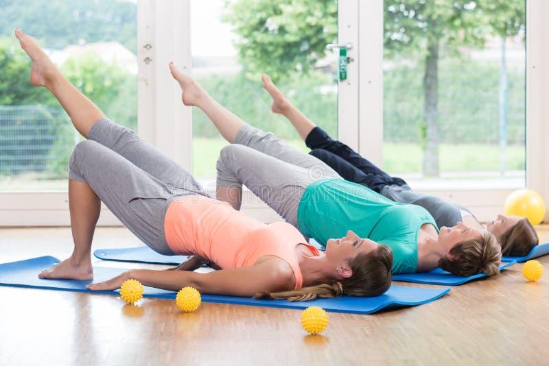 Γυναίκες που κάνουν τις ασκήσεις για το πάτωμα λεκανών στη μεταγεννητική σειρά μαθημάτων στοκ φωτογραφία με δικαίωμα ελεύθερης χρήσης