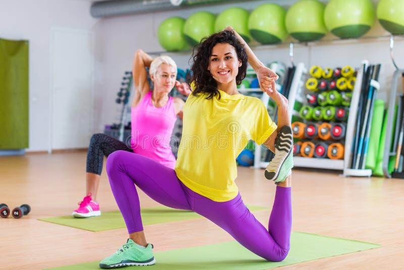 Γυναίκες που κάνουν τις τεντώνοντας ασκήσεις γιόγκας στο χαλί στο εσωτερικό στη γυμναστική στοκ εικόνα