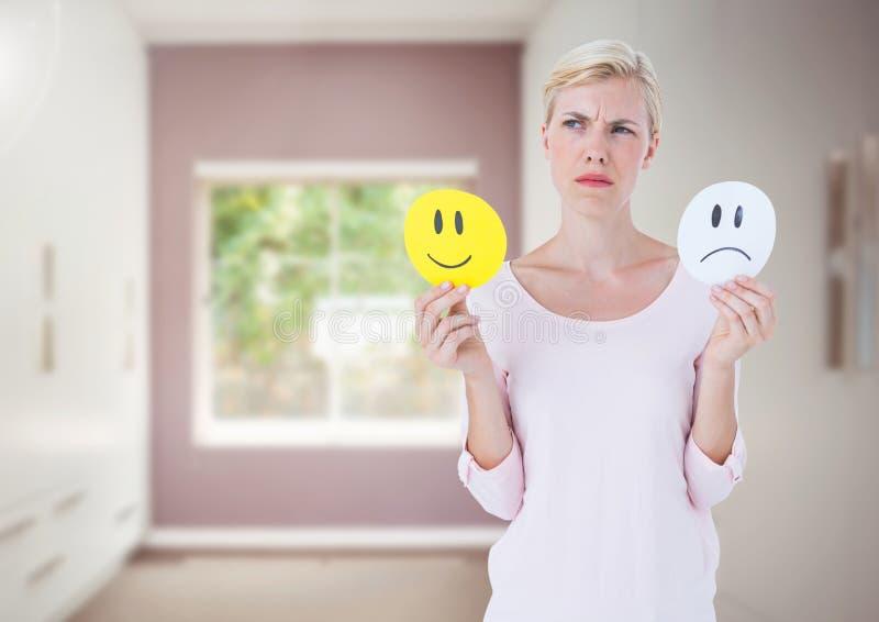 Γυναίκες που κρατούν τα πρόσωπα που αποφασίζουν τις ευτυχείς ή λυπημένες συγκινήσεις ενάντια στο δωμάτιο στοκ εικόνες