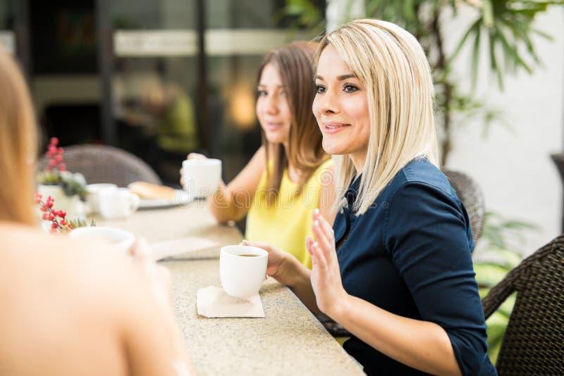 Γυναίκες που μοιράζονται κάποιο κουτσομπολιό πέρα από τον καφέ στοκ εικόνα με δικαίωμα ελεύθερης χρήσης