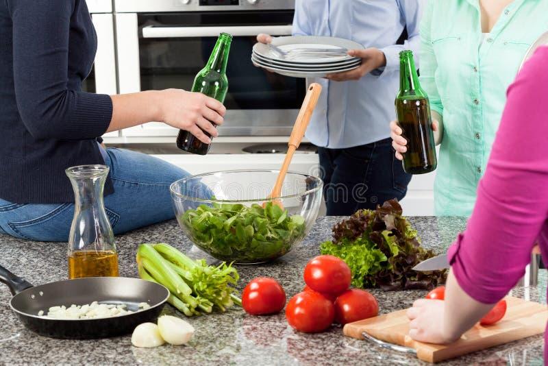 Γυναίκες που πίνουν την μπύρα και που προετοιμάζουν τα τρόφιμα για το κόμμα στοκ εικόνες