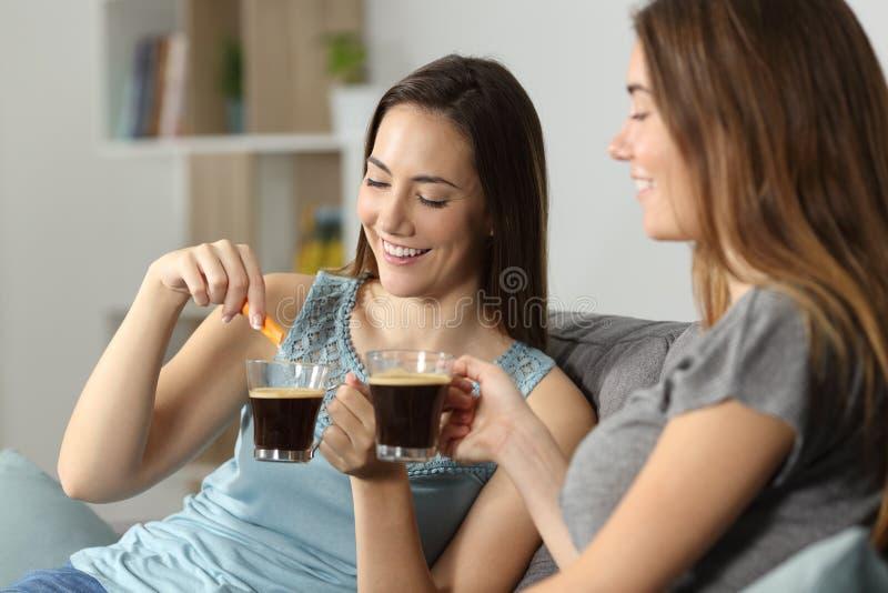 Γυναίκες που πίνουν τον καφέ που ρίχνει τη ζάχαρη στο φλυτζάνι στοκ εικόνα