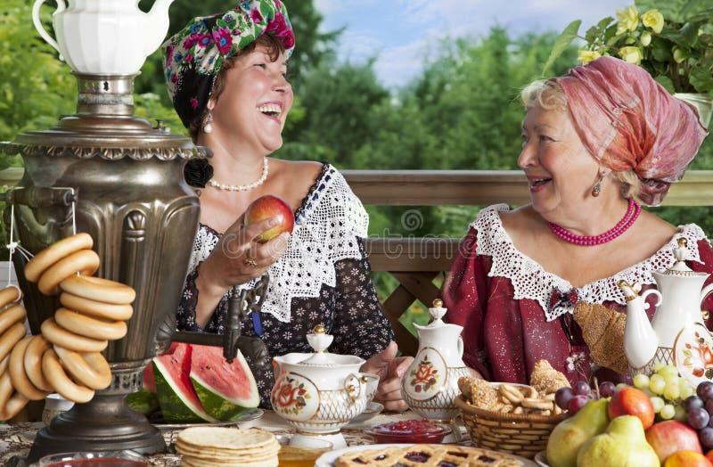Γυναίκες που πίνουν το τσάι υπαίθρια στοκ εικόνες
