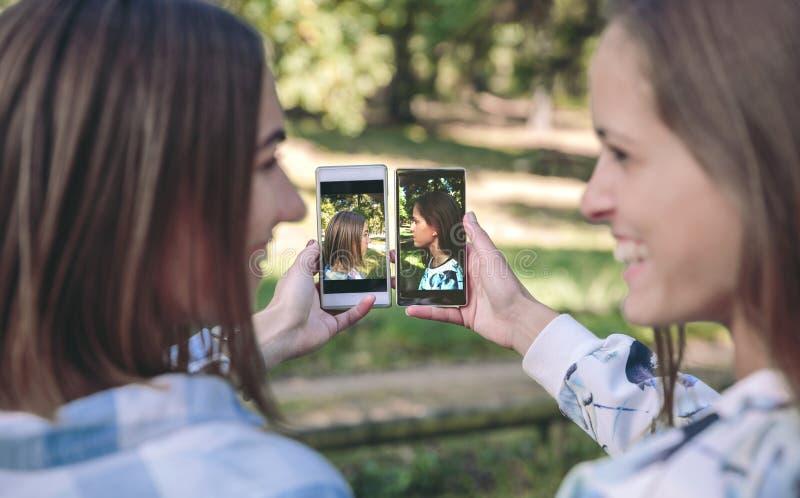 Γυναίκες που παρουσιάζουν smartphones με τις φωτογραφίες πορτρέτων πλάγιας όψης στοκ φωτογραφίες