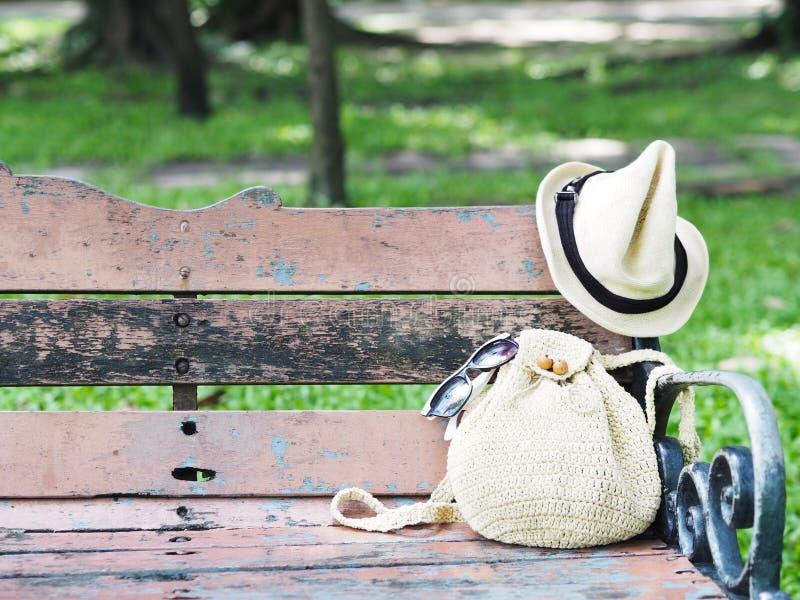 Γυναίκες που πλέκουν την τσάντα και το καπέλο στον εκλεκτής ποιότητας ξύλινο πάγκο στο πάρκο στοκ εικόνες με δικαίωμα ελεύθερης χρήσης