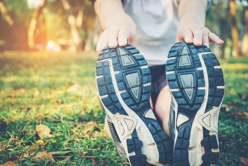 Γυναίκες που τεντώνουν μετά από τον αθλητισμό στη χλόη στοκ εικόνες
