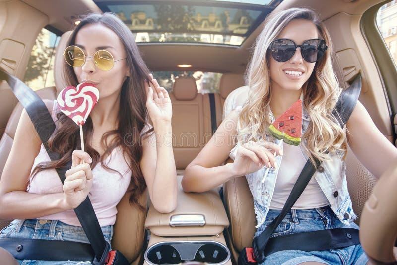 Γυναίκες που τρώνε τα μεγάλα lollipops στο αυτοκίνητο πολυτέλειας στοκ εικόνες