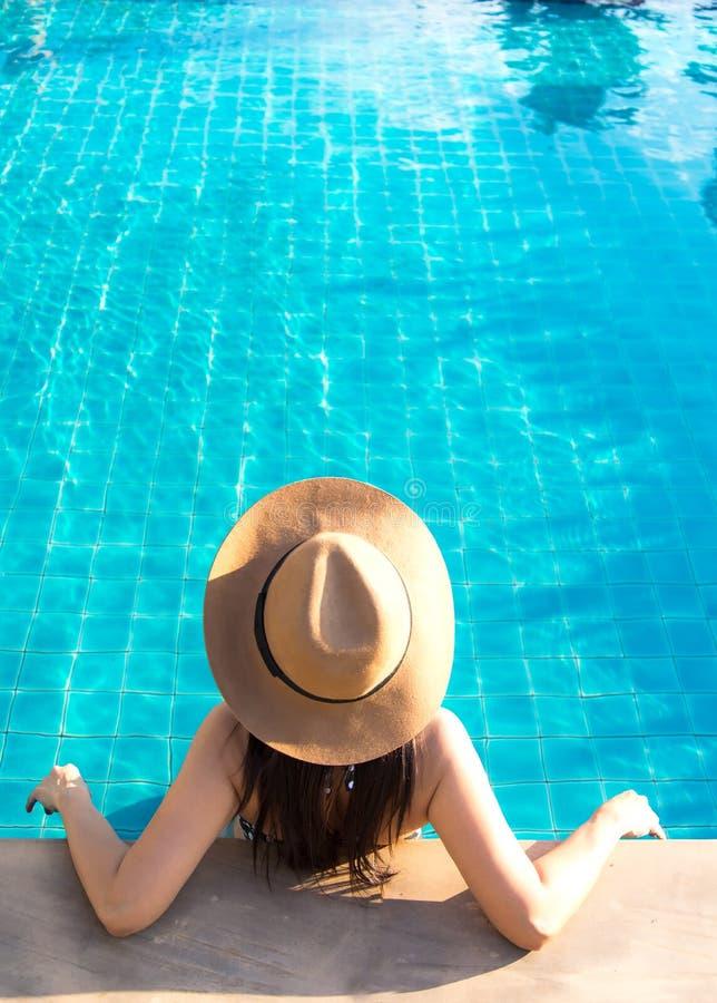 Γυναίκες που χαλαρώνουν κοντά στην κολύμβηση πολυτέλειας στοκ φωτογραφία με δικαίωμα ελεύθερης χρήσης