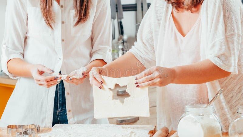 Γυναίκες που ψήνουν τη ζύμη εκμετάλλευσης που κατασκευάζει τα μπισκότα στοκ φωτογραφίες