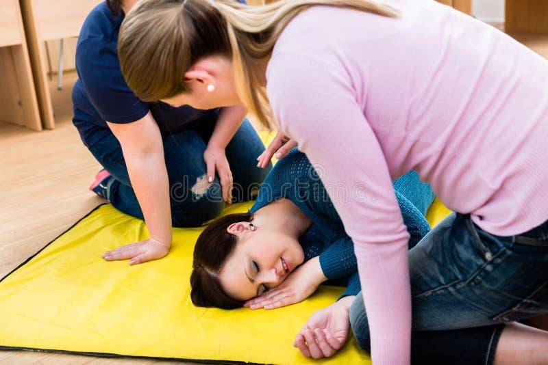 Γυναίκες στην κατηγορία πρώτων βοηθειών που εκπαιδεύουν να τοποθετήσει το τραυματισμένο πρόσωπο στοκ φωτογραφίες