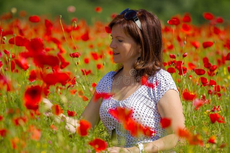 Γυναίκες στις κόκκινες παπαρούνες στοκ εικόνες με δικαίωμα ελεύθερης χρήσης