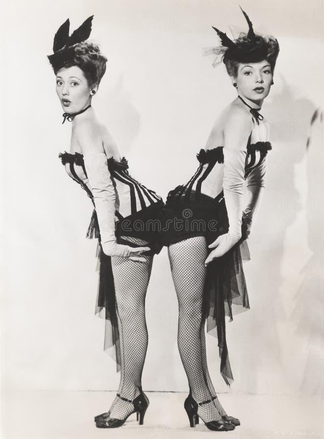 Γυναίκες στο ταίριασμα των κοστουμιών που στέκονται πλάτη με πλάτη στοκ εικόνες