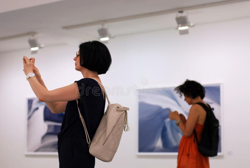 Γυναίκες στο exhition φωτογραφιών που χρησιμοποιούν smartphones, τις κινητές συσκευές και τον κοινωνικό εθισμό δικτύων στοκ φωτογραφία με δικαίωμα ελεύθερης χρήσης