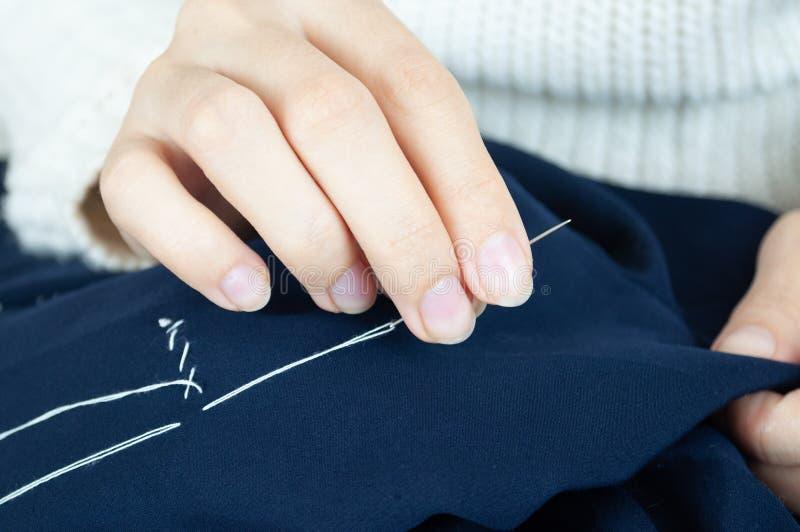 Γυναικεία δάκτυλα με νήματα και υφάσματα για ραφή βελόνας Ραπτική, επισκευή ενδυμάτων στοκ φωτογραφίες