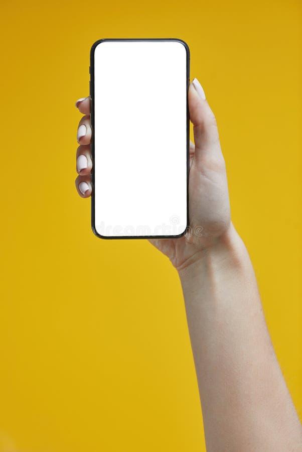 Γυναικεία χέρια κρατώντας smartphone σε κίτρινο φόντο στοκ φωτογραφία με δικαίωμα ελεύθερης χρήσης