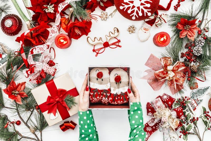 Γυναικεία χέρια με πράσινη μπλούζα που κρατά ανοιχτό κουτί δώρου με αστείες κάλτσες ελαφιού σε λευκό φόντο με κόκκινα χριστουγενν στοκ εικόνα