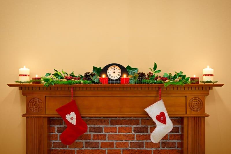 Γυναικείες κάλτσες και γιρλάντα Χριστουγέννων σε ένα mantlepiece στοκ εικόνες