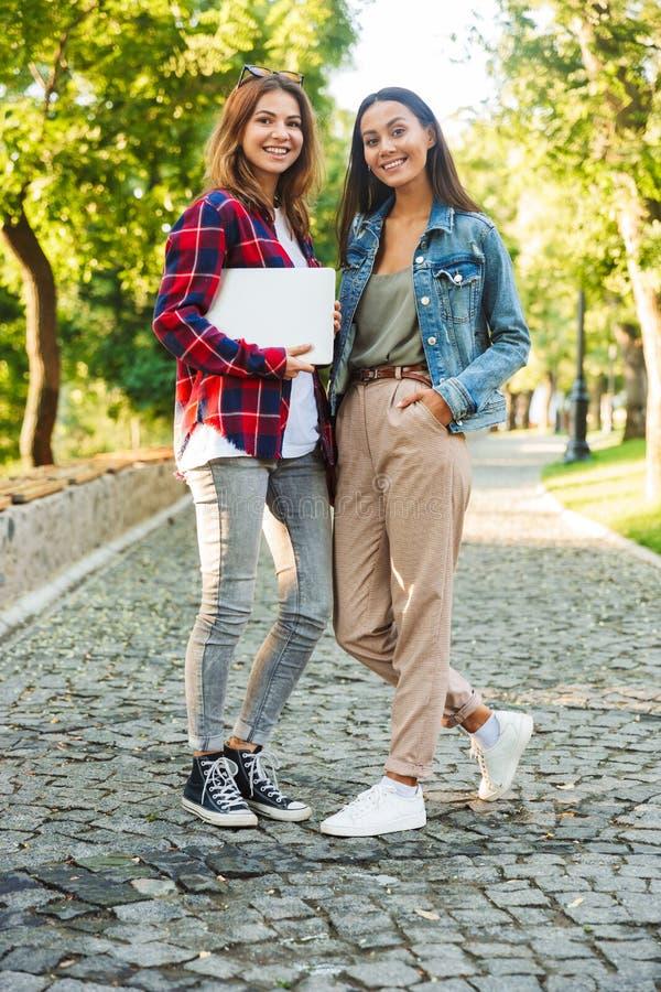 Γυναικείοι σπουδαστές που περπατούν στο φορητό προσωπικό υπολογιστή εκμετάλλευσης πάρκων στοκ εικόνα