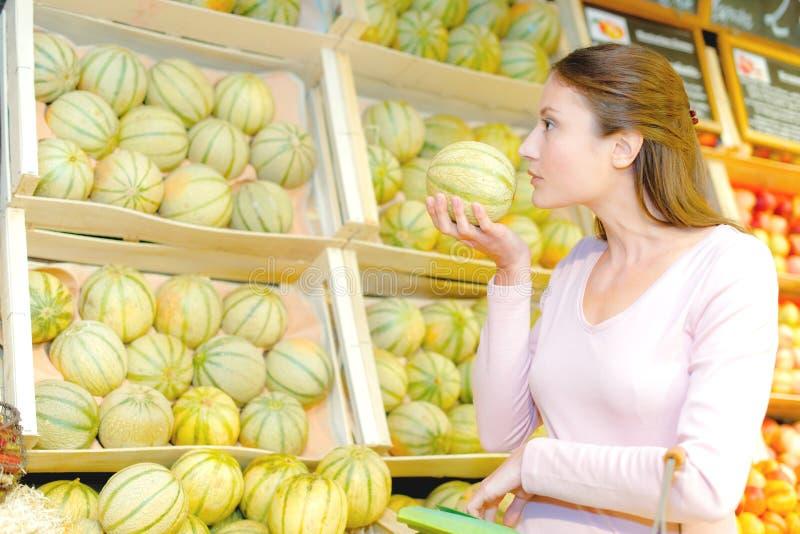 Γυναικείο μυρίζοντας πεπόνι για ripeness στοκ εικόνα με δικαίωμα ελεύθερης χρήσης