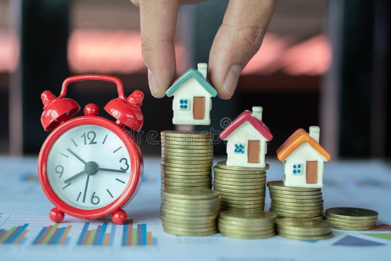Γυναικείο σπίτι, σε κέρμα μοντέλο οικίας για τη χρηματοδότηση και την τραπεζική έννοια ξυπνητήρι, επένδυση ακινήτων, στοκ φωτογραφία με δικαίωμα ελεύθερης χρήσης
