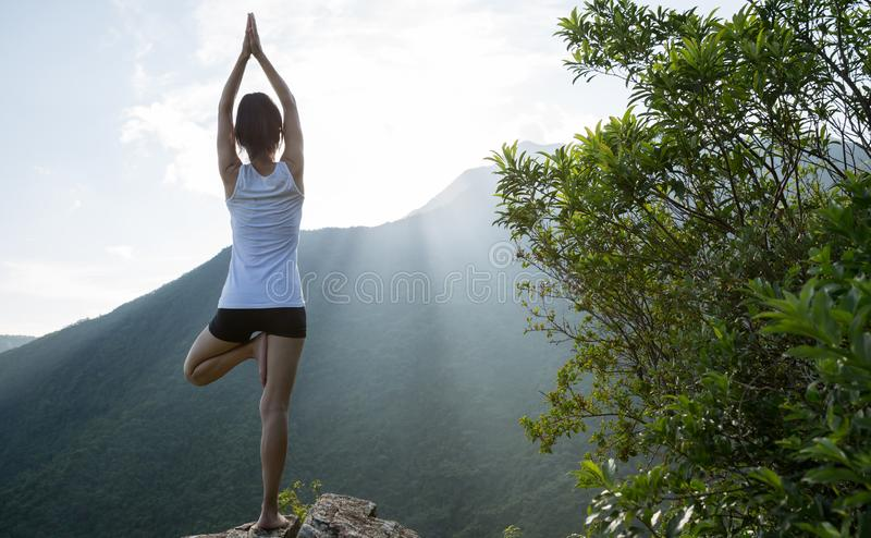 Γυναικών γιόγκας στη μέγιστη άκρη απότομων βράχων βουνών στοκ φωτογραφίες