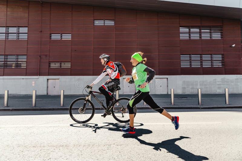 γυναικών δρομέων τρέχοντας τρέξιμο θύελλας γύρων ποδηλατών οδών επόμενο το Μάιο στοκ εικόνες