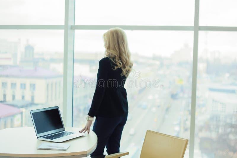 Γυναικών ξανθή εργαζομένων πόλη άποψης παραθύρων γραφείων μεγάλη στοκ φωτογραφίες με δικαίωμα ελεύθερης χρήσης