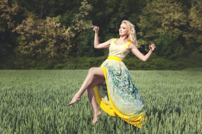 Γυναικών πέρα από τον τομέα μια ηλιόλουστη ημέρα στοκ εικόνες