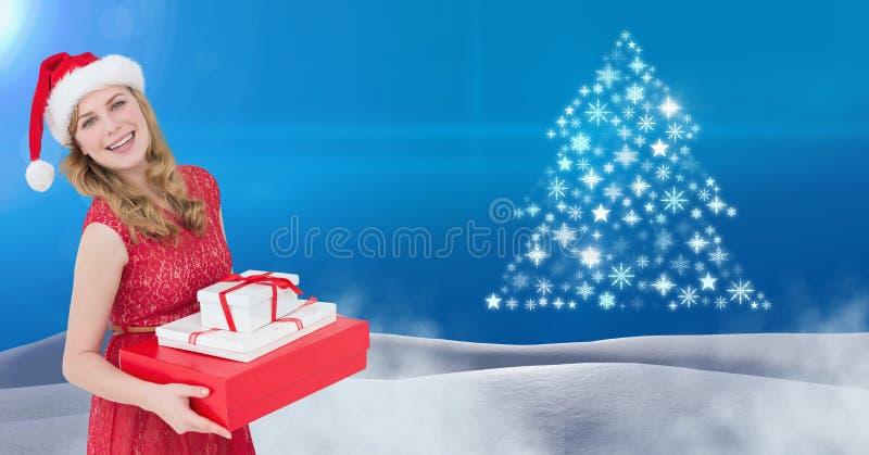 Γυναικών Santa εκμετάλλευσης κιβωτίων και Snowflake δώρων μορφή σχεδίων χριστουγεννιάτικων δέντρων στο τοπίο χιονιού στοκ φωτογραφίες