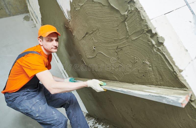 Γυψαδόρος που λειαίνει το φρέσκο ασβεστοκονίαμα στον τοίχο από το straightedge trowel στοκ εικόνα με δικαίωμα ελεύθερης χρήσης