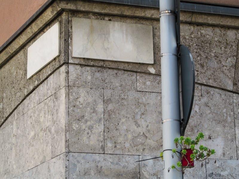 Γωνία του δρόμου με τα κενά σημάδι-πιάτα γρανίτη και ενιαίες εγκαταστάσεις flowerpot που κρεμά σε έναν σωλήνα στοκ εικόνες