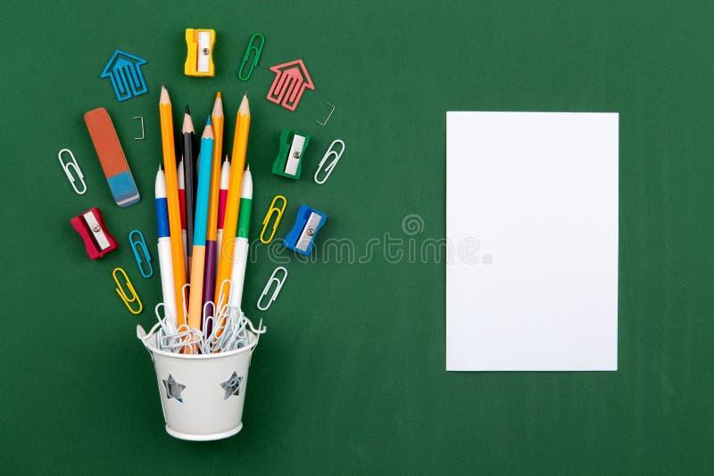 Γόμα μανδρών συνδετήρων εγγράφου μολυβιών χαρτικών σε έναν άσπρο κάδο Ακόμα ζωή στο πράσινο υπόβαθρο σχολικών πινάκων Το διαστημι στοκ φωτογραφία με δικαίωμα ελεύθερης χρήσης
