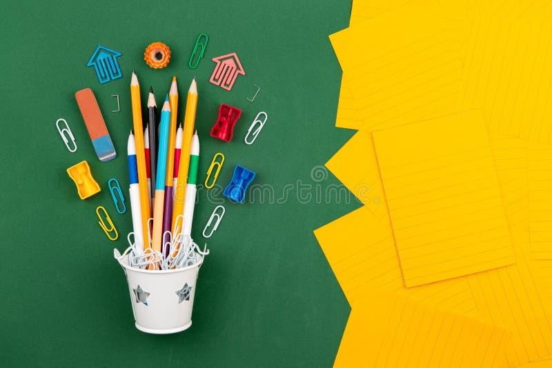 Γόμα μανδρών συνδετήρων εγγράφου μολυβιών χαρτικών σε έναν άσπρο κάδο Ακόμα ζωή στο πράσινο υπόβαθρο σχολικών πινάκων Το διαστημι στοκ εικόνες