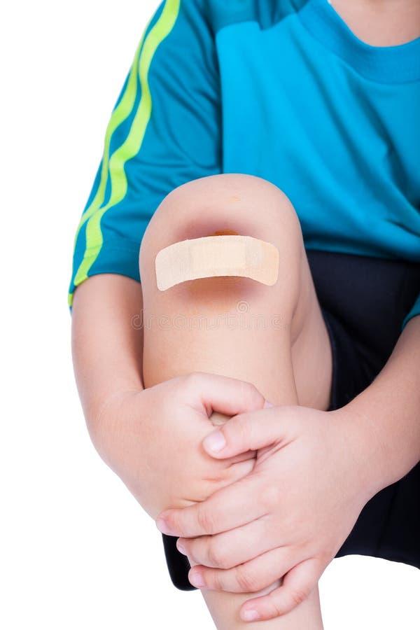 Γόνατο παιδιών με ένα ασβεστοκονίαμα (για τις πληγές) και το μώλωπα στοκ φωτογραφίες