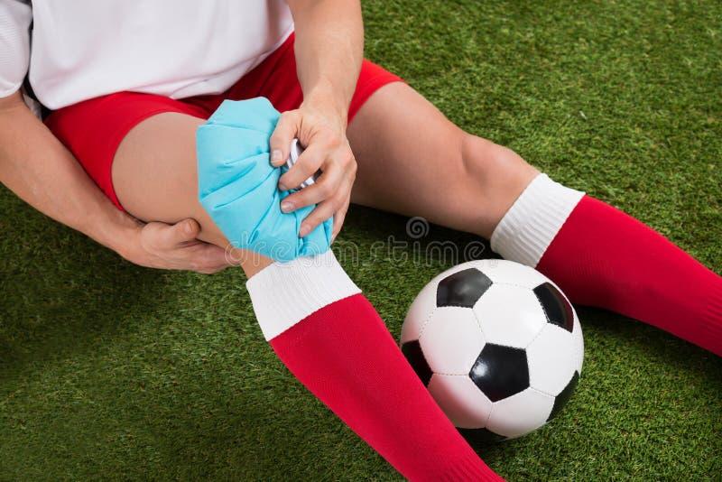 Γόνατο τήξης ποδοσφαιριστών με το πακέτο πάγου στοκ εικόνα
