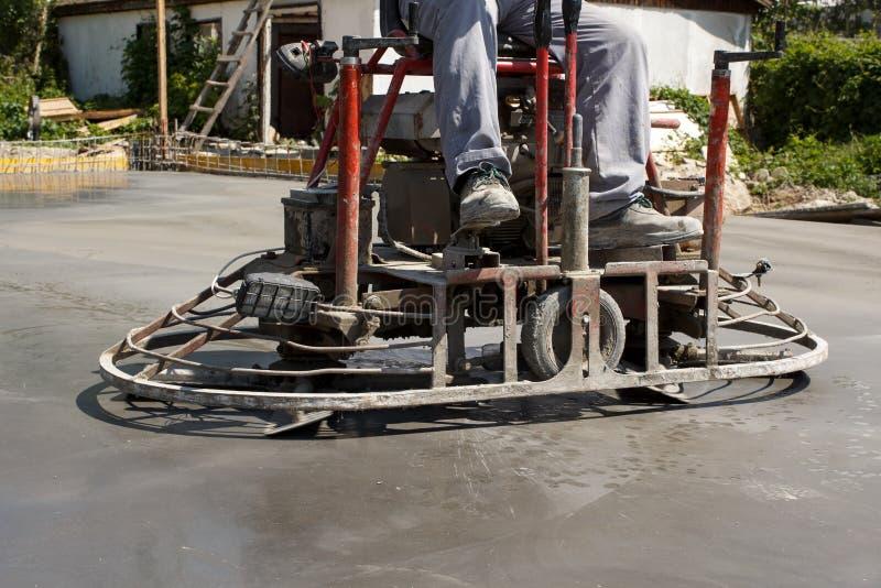 Γύρος εργασίας στη μηχανή δύναμης trowel σε μια τσιμεντένια πλάκα στοκ εικόνα