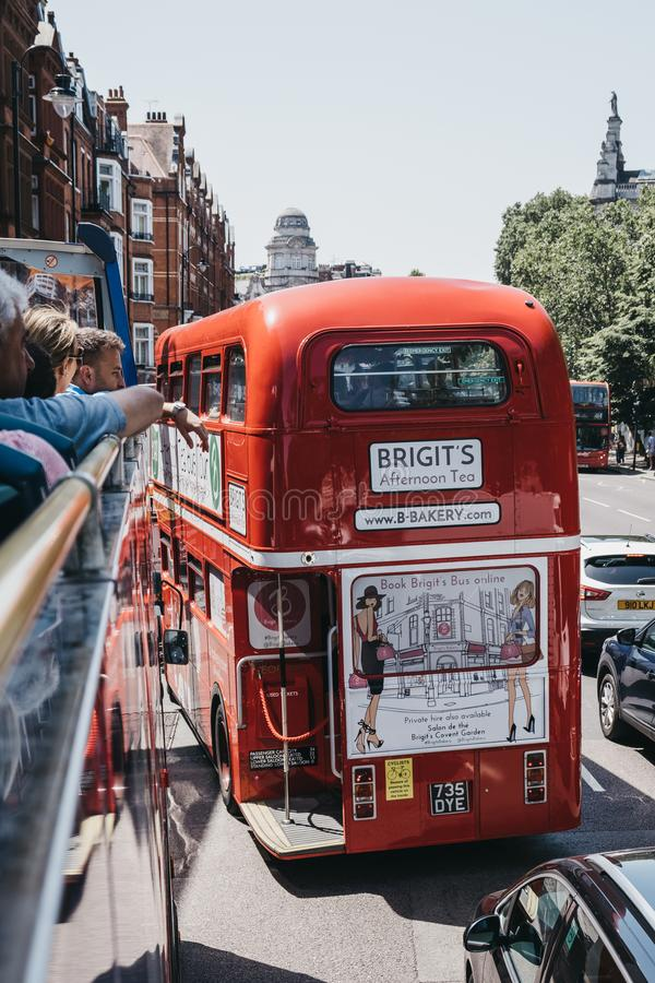Γύρος λεωφορείων τσαγιού απογεύματος Bridgits μέσα στο αναδρομικό κόκκινο διπλό λεωφορείο καταστρωμάτων σε μια οδό στο Λονδίνο, U στοκ φωτογραφίες