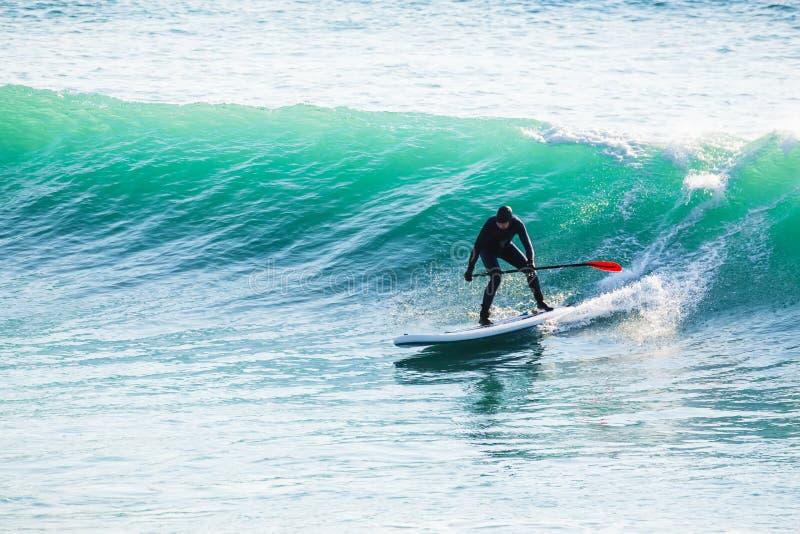 Γύρος Surfer στη στάση επάνω στον πίνακα κουπιών στα ωκεάνια κύματα Στάση επάνω στο κουπί που επιβιβάζεται στη θάλασσα στοκ εικόνες