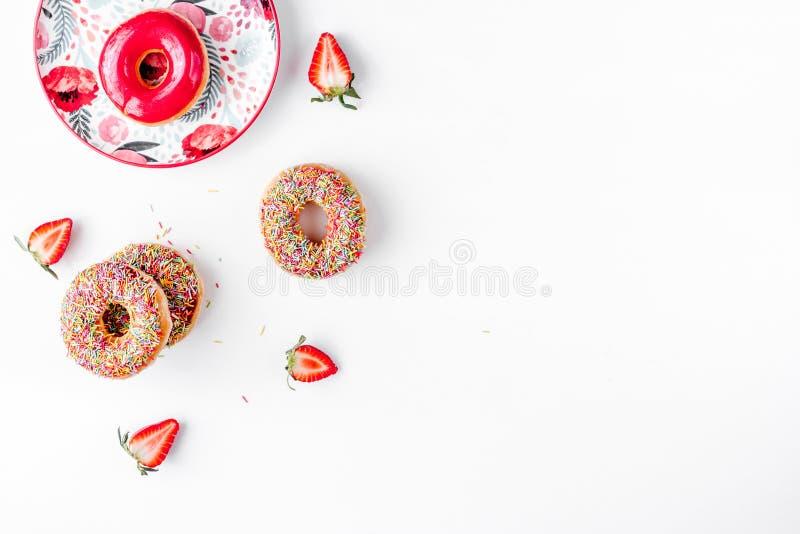 Γλυκά ζωηρόχρωμα donuts με καλύμματος το άσπρο γραφείων πρότυπο άποψης υποβάθρου τοπ στοκ φωτογραφία με δικαίωμα ελεύθερης χρήσης