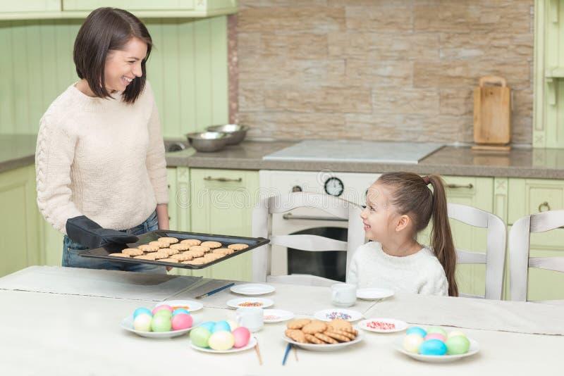 Γλυκά μπισκότα ψησίματος κοριτσιών με τη μητέρα της στοκ φωτογραφίες