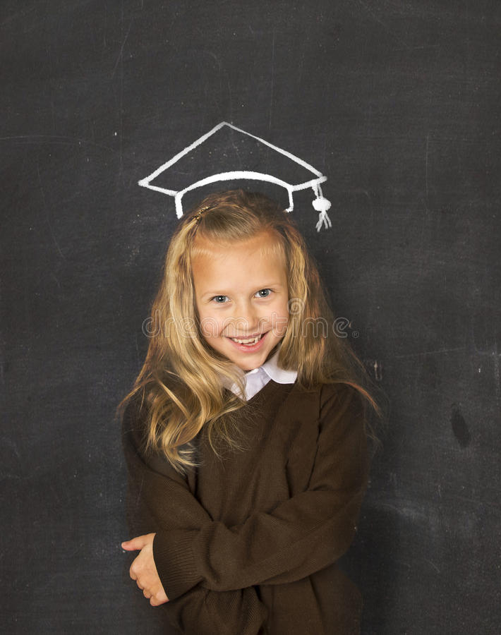 Γλυκιά μαθήτρια στον πίνακα με με το σχέδιο σκίτσων κιμωλίας του χαμόγελου καπέλων βαθμολόγησης ευτυχούς στοκ φωτογραφίες